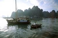 Vietnam, Halong Bay, woman rowing boat. - Steve Raymer