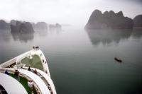 Vietnam, Halong Bay, cruise ship and small fishing boat. - Steve Raymer