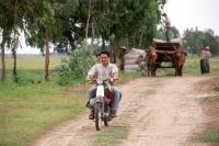 Vietnam, Thay Ninh, man riding motorbike on bumpy road. - Steve Raymer