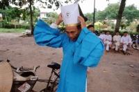 Vietnam, Tay Ninh, Cao Dai priest arranging hat. - Steve Raymer