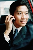 Male executive in car, talking on cellular phone - Gareth Brown