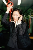 Female executive in subway train, talking on cellular phone - Gareth Brown