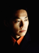 Male executive looking away, portrait, black background - Jade Lee