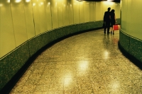 Hong Kong, man and woman walking in MTR (subway) station - Jade Lee