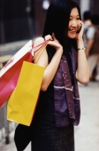 Woman talking on cellular phone, holding shopping bags - Jade Lee