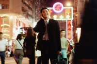 Hong Kong, male executive using cellular phone, carrying briefcase - Jade Lee