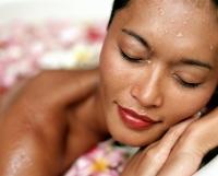 Woman relaxing in bathtub with flower petals, eyes closed - Jack Hollingsworth