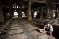 Singapore, Arab Street, Muslim man reads Koran in Mosque. - Steve Raymer