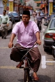 Malaysia, Malacca, Muslim man on bicycle. - Steve Raymer