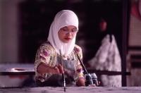 Malaysia, Kuala Terengganu, Muslim woman wearing tudung paints fabric at batik factory. - Steve Raymer