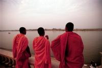 Cambodia, Phnom Penh, Buddhist monks watching the muddy, slow-moving Mekong River along a riverfront promenade. - Steve Raymer