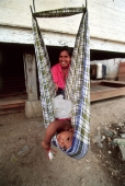 Indonesia, Aceh, Banda Aceh, Mother cares for child in makeshift swing. - Steve Raymer