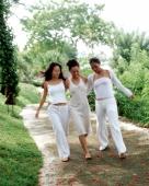 Three women wearing white strolling down path - Jack Hollingsworth