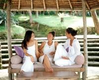 Three women wearing white, sitting together on bench talking - Jack Hollingsworth
