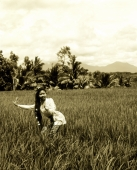 Indonesia, Bali, Balinese dancer in fields, trees in background - Jack Hollingsworth