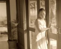 Woman leaning on door frame, looking down - Jack Hollingsworth