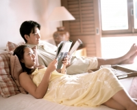 Woman and man in bed reading magazines. - Jack Hollingsworth