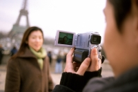 Man videotaping woman in front of Eiffel Tower, focus on camcorder. - Leila  Pivetta