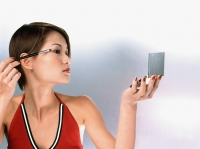 Profile of woman applying mascara, white background - Eric Ceret