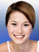 Young woman smiling, blue background, portrait - Eric Ceret