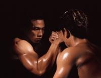 Two men arm wrestling, black background - Eric Ceret