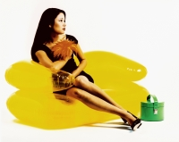 Young woman sitting on yellow inflatable chair, green purse - Erik Soh