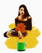 Young woman sitting on yellow inflatable chair, holding green purse - Erik Soh