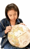 Young girl looking at globe. - Jade Lee