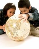 Young girl and boy looking at globe. - Jade Lee