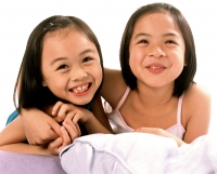 Two young girls embracing, laughing, white background. - Jade Lee