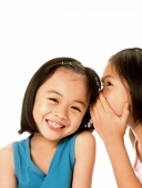 Two young girls whispering to each other, laughing, white background. - Jade Lee