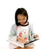 Young girl reading book, white background. - Jade Lee