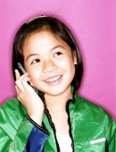 Young girl using cellular phone, smiling, purple background. - Jade Lee