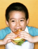 Young boy eating large hamburger, yellow background. - Jade Lee