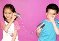Children playing with toy string telephone, purple background. - Jade Lee