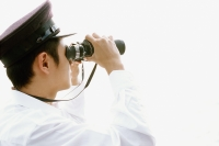 Profile of man in white looking through binoculars, white background - Eric Ceret