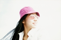 Young woman with purple hat and sunglasses looking away, white background - Eric Ceret