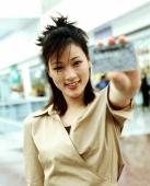 Woman holding up credit card, shops in background, portrait. - Jack Hollingsworth