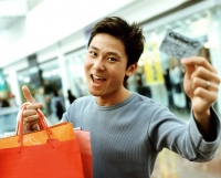 Young man holding shopping bags and credit card, smiling. - Jack Hollingsworth