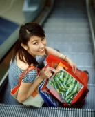 Woman holding shopping bags sitting on escalator. - Jack Hollingsworth