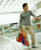 Casual dressed man holding shopping bags in mall leaning on railing. - Jack Hollingsworth