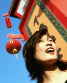 Woman laughing next to chinese sign, lantern and blue sky in background. - Jack Hollingsworth