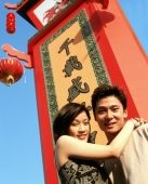 Couple embracing in front of chinese sign, lantern and blue sky in background. - Jack Hollingsworth