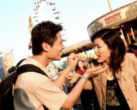 Man feeding fishballs to woman at carnival. - Jack Hollingsworth