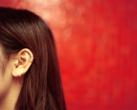 Profile of ear and hair of young woman, red background. - Jack Hollingsworth