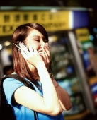 Young woman using cellular phone, laughing, shops in background. - Jack Hollingsworth