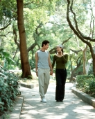 Young couple walking down path holding hands, nature in background. - Jack Hollingsworth