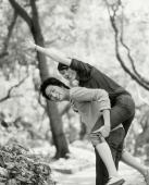 Young man piggybacking woman on nature path. - Jack Hollingsworth