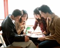 Group of friends eating pretzels, looking at magazine. - Jack Hollingsworth