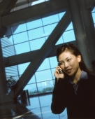 Executive woman using cellular phone indoors, windows in background. - Jack Hollingsworth